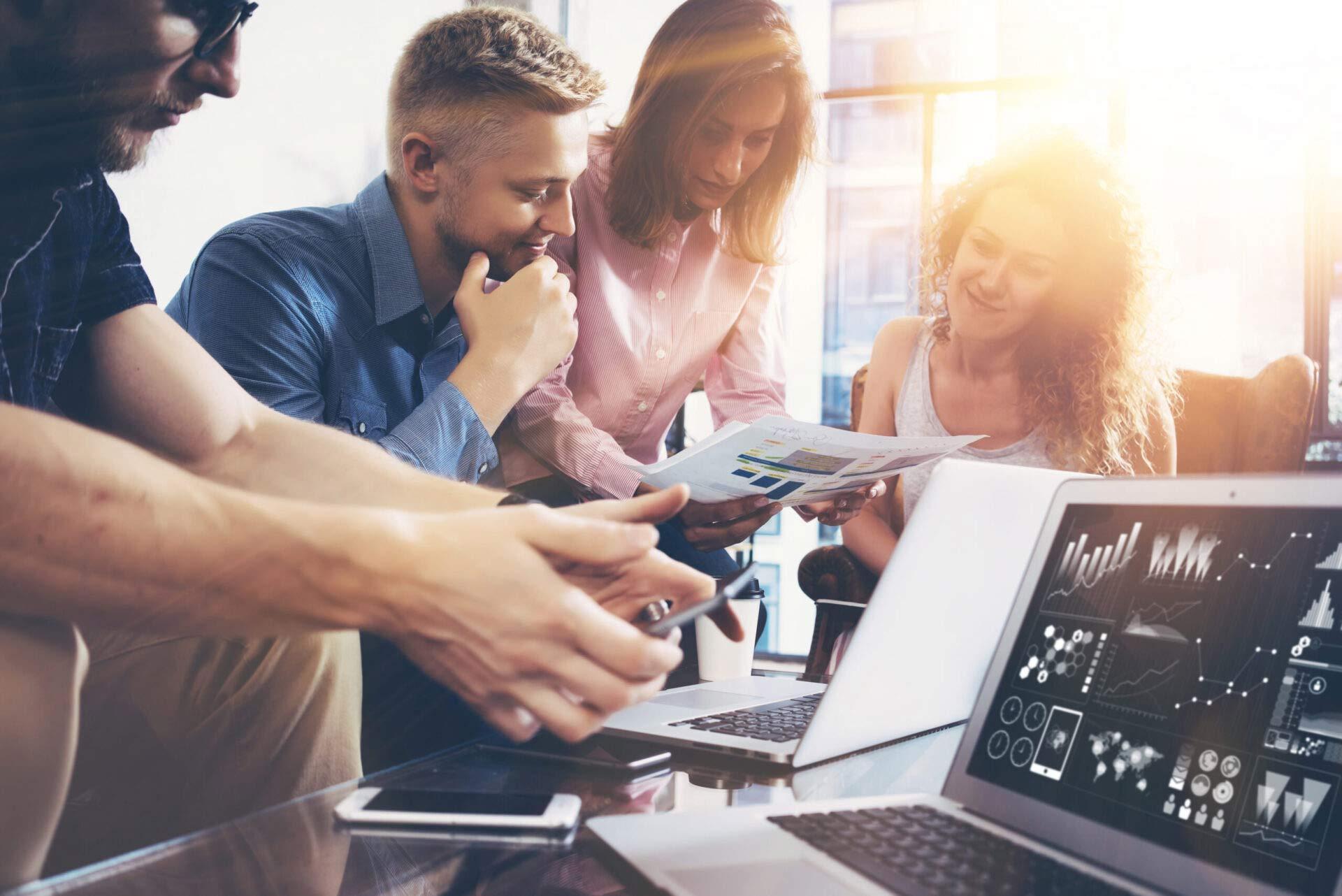 Marketing Team schaut Laptop Hell netcom GmbH